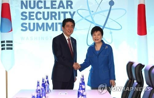 This photo, taken on March 31, 2016, shows President Park Geun-hye shaking hands with Japanese Prime Minister Shinzo Abe before their talks on the sidelines of the National Security Summit in Washington, D.C. (Yonhap)