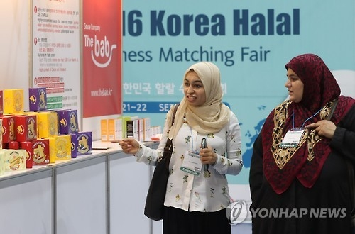 Two women wearing hijab pass by halal food products displayed in a Seoul trade show on July 21, 2016. (Yonhap)