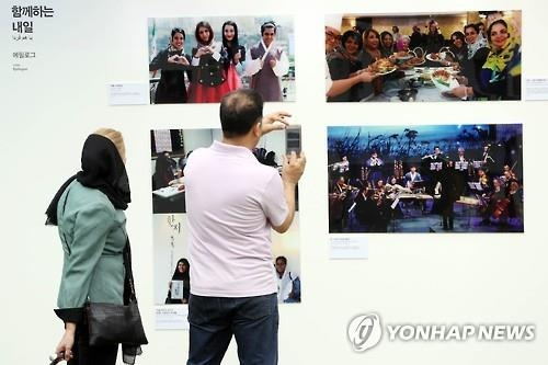 Visitors look at photos on display at a special photo exhibition that marks the long-standing friendship between South Korea and Iran at the National Museum of Korean Contemporary History in Seoul on Sept. 28, 2016. (Yonhap)