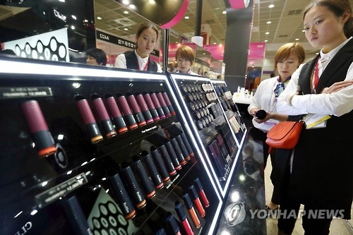 A woman looks at color makeup products during a cosmetics exhibition at COEX in Seoul on April 28, 2016. (Yonhap)