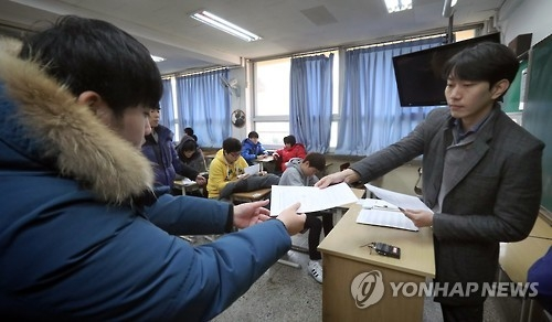 A high school senior receives his score on the state-administrated scholastic aptitude test from his homeroom teacher at Yeouido High School in Seoul on Dec. 7, 2016. High scores on the test, administered last month, boost students' chances of entering the university of their choice. (Yonhap)