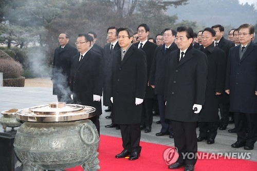 Acting President and Prime Minister Hwang Kyo-ahn (C) pays his respects at the Seoul National Cemetery in central Seoul on Jan. 1, 2017. (Yonhap)