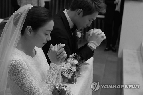 In this photo provided by the Rain Company, singer-actor Rain and actress Kim Tae-hee pray during their wedding at Gahoe-dong Church in central Seoul on Jan. 19, 2017. (Yonhap)