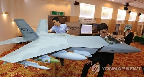 In this photo taken on June 14, 2016, military officials take a look at a KF-X model aircraft displayed during an exhibition held in an Air Force building in Seoul. (Yonhap)
