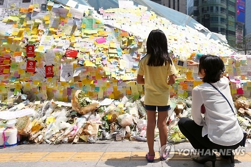 This file photo taken on May 22, 2016, shows citizens looking at a myriad of Post-it condolence messages on the wall of a subway exit in southern Seoul, which citizens voluntarily left to mourn a 22-year-old woman who was brutally murdered. The victim was fatally stabbed by a stranger in a bathroom near Gangnam Subway Station the previous week, sparking a nationwide outpouring of mourning. (Yonhap)