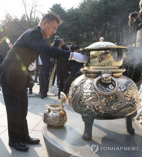 Moon Jae-in, the presidential candidate of the liberal Democratic Party of Korea, burns incense in front of the tomb of late President Park Chung-hee, the father of ousted leader Park Geun-hye, during a visit to a national cemetery in Seoul on April 4, 2017. (Yonhap)