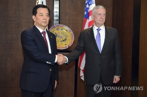 South Korean Defense Minister Han Min-koo (L) shakes hands with U.S. Secretary of Defense Jim Mattis in their meeting held on the sidelines of the 16th Asia Security Summit in Singapore on June 3, 2017. (AP-Yonhap)