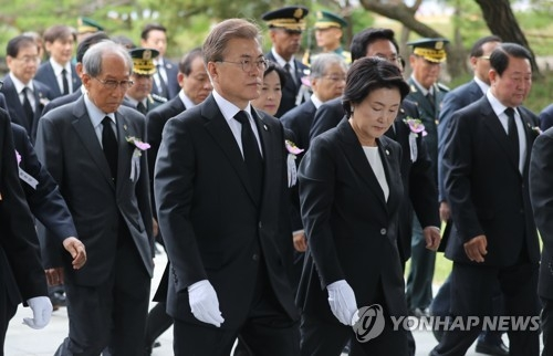 President Moon Jae-in (second from L) and his wife Kim Jung-sook walk toward their seats after paying their respects to national heroes buried at the National Cemetery in Seoul before the start of a ceremony marking Memorial Day on June 6, 2017. (Yonhap)