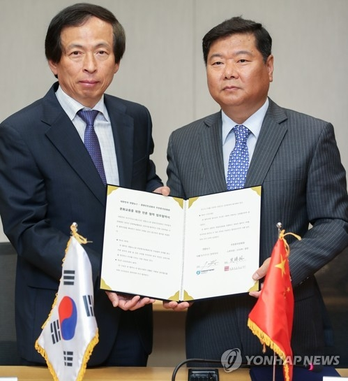 Lee Hong-ki (L), Yonhap News Agency's executive director, shakes hands with the director of the Chinese Cultural Center in Seoul on June 7, 2017. (Yonhap)
