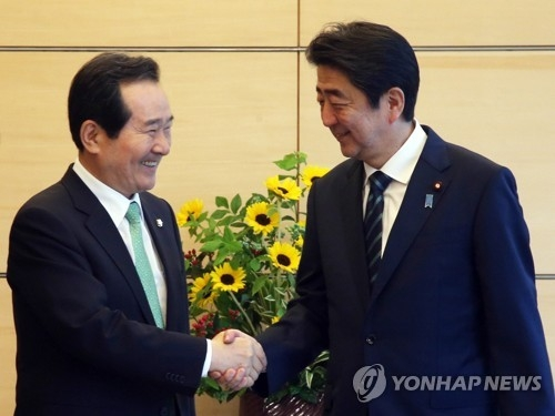 South Korea's National Assembly Speaker Chung Sye-kyun (L) shakes hands with Japanese Prime Minister Shinzo Abe during their meeting at his official residence in Tokyo on June 8, 2017, in this photo provided by the Assembly. (Yonhap)
