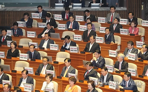 Representatives of the main opposition Liberty Korea Party listen to President Moon Jae-in's address to the nation at the National Assembly on June 12, 2017. The opposition lawmakers had small signposts in front of their desk-top screens, urging the Moon administration to withdraw some of its nominations for new ministers. (Yonhap)