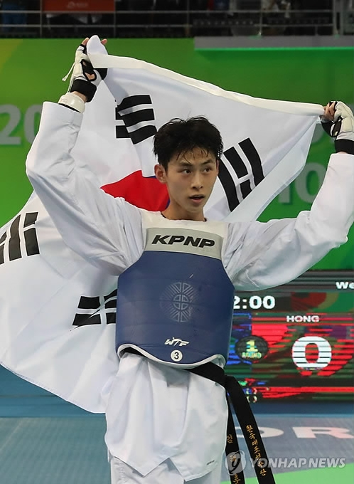 Kim Tae-hun of South Korea lifts his national flag in celebration of his gold medal in the men's under-54kg at the World Taekwondo Federation (WTF) World Taekwondo Championships at Taekwondowon's T1 Arena in Muju, North Jeolla Province, on June 25, 2017. (Yonhap)