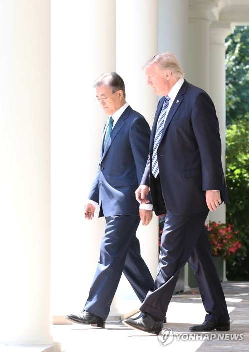 South Korean President Moon Jae-in (L) and U.S. President Donald Trump walk side by side on their way to the White House Rose Garden where they held a joint press conference following their summit talks on June 30, 2017. (Yonhap)