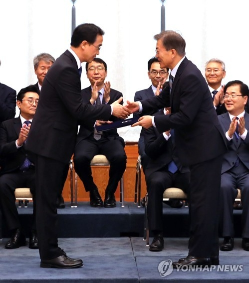 President Moon Jae-in (R) shakes hands with his new Unification Minister Cho Myung-gyun after representing him with a certificate of appointment in a ceremony held at the presidential office Cheong Wa Dae on July 3, 2017. The ceremony also involved new agriculture minister Kim Yung-rok and new head of the National Tax Service Han Seung-hee. (Yonhap)