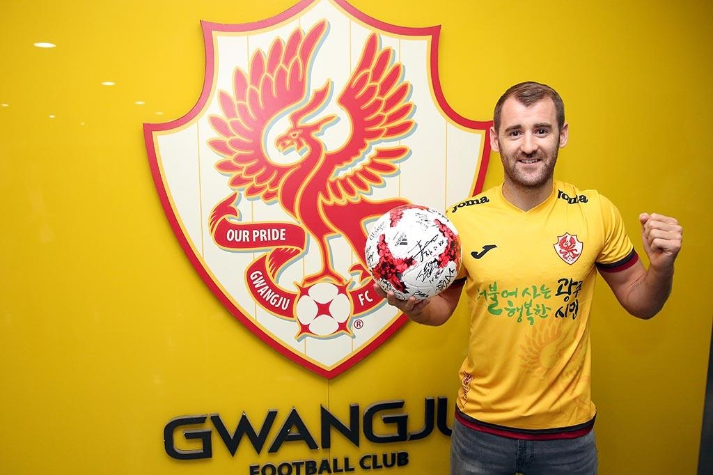 In this photo released by Gwangju FC on July 4, 2017, Northern Irish footballer Niall McGinn poses for a photo in front of the club emblem. (Yonhap)