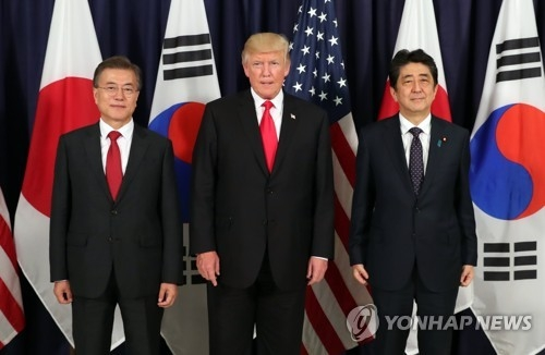 South Korean President Moon Jae-in (L), U.S. President Donald Trump (C) and Japanese Prime Minister Shinzo Abe pose for a photograph before the start of a three-way meeting at the U.S. consulate in Hamburg, Germany on July 6, 2017. (Yonhap)