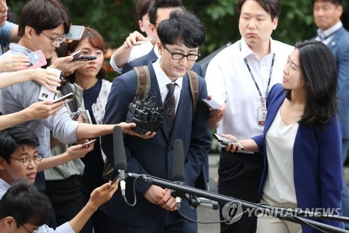 Lee Jun-seo, a former senior member of the minor opposition People's Party suspected of taking part in a fake tip-off scandal, is surrounded by reporters asking questions as he enters the courthouse for a hearing on his arrest warrant in Seoul on July 11, 2017. (Yonhap)