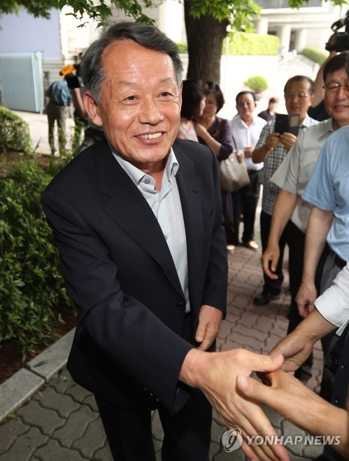 Retired Adm. Choi Yoon-hee, former chairman of the Joint Chiefs of Staff, with a smiling face, shakes hands with his acquaintances after he was acquitted by an appeals court of bribery charges in connection with a military chopper lobbying scandal, in Seoul on July 13, 2017. (Yonhap)