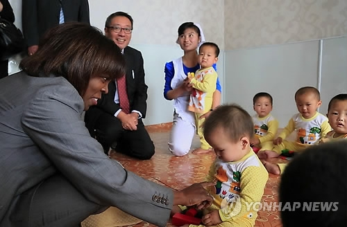 This photo provided by the World Food Program (WFP) and Marco Frattini on May 24, 2014, shows WFP Executive Director Ertharin Cousin (L) meeting with North Korean children at a nursery facility during her visit to North Korea. (Yonhap)