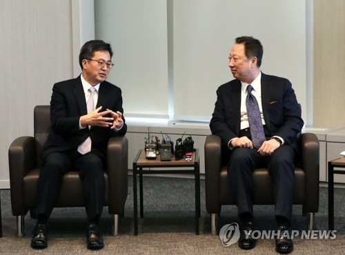 Finance Minister Kim Dong-yeon (L) speaks with Park Yong-maan, chairman of the Korean Chamber of Commerce and Industry, in a meeting in Seoul on Dec. 8. (Yonhap)