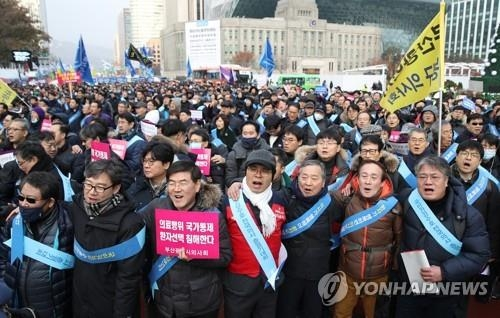 In this photo taken Dec. 10, 2017, doctors stage a rally against the government's medicare program, which they claim will drive down their earnings. (Yonhap)