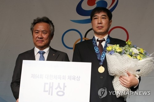 Kim Nam-soo (R), father of speed skater Kim Min-seok, wears the gold medal presented to him by Lee Kee-heung (L), president of the Korean Sport & Olympic Committee (KSOC), during the KSOC Awards ceremony in Seoul on Feb. 28, 2018. Kim Min-seok was named the grand prize winner for 2017 but wasn't able to attend the ceremony because of an overseas competition. (Yonhap)