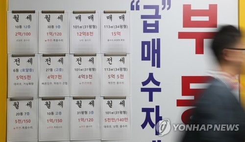 In this file photo taken on Oct. 8, 2017, a passerby walks in front of a realtor's office displaying signs for home leases and home sales. (Yonhap)