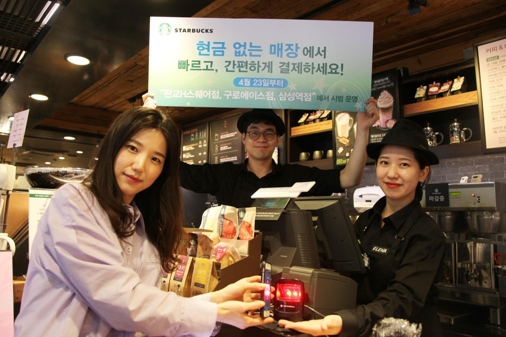 In this undated photo provided by Starbucks Coffee Korea Co., the local unit of the U.S. coffee giant, models pose for a photo to advertise the test operation of cashless stores in South Korea set to kick off April 23, 2018. (Yonhap)