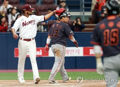 In this photo provided by the Nexen Heroes baseball club, Esmil Rogers of the Heroes (L) taps Choi Jae-hoon of the Hanwha Eagles on the helmet after Choi was thrown out at home during the second inning of the teams' Korea Baseball Organization regular season game at Gocheok Sky Dome in Seoul on March 24, 2018. (Yonhap)