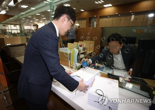 An official from Hannuri Law hands over documents related to its lawsuit against Apple Inc. and its local branch to the Seoul Central District Court in the nation's capital on March 30, 2018. (Yonhap)