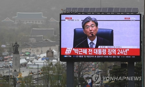 This photo, taken from a long shot in central Gwanghwamun, captures the moment in a live televised corruption trial of former President Park Geun-hye on April 6, 2018, that the judge metes out a 24-year prison sentence for the disgraced leader. (Yonhap)
