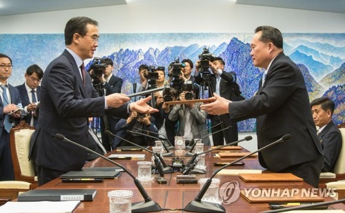 This photo, taken by the Joint Press Corps on June 1, 2018, shows South Korea's chief delegate Cho Myoung-gyon (L) and his North Korean counterpart Ri Son-gwon exchange a joint press statement issued after their hourslong high-level talks held at the truce village of Panmunjom. (Yonhap)