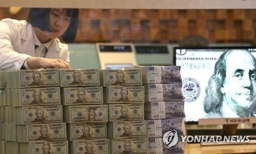 This file photo shows a South Korean bank employee checking U.S. dollar bills and other foreign banknotes. (Yonhap)