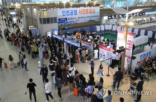 This photo, taken June 8, 2018, shows South Koreans lining up to cast ballots in early voting for the June 13 local elections and parliamentary by-elections at Incheon International Airport before departure. (Yonhap)