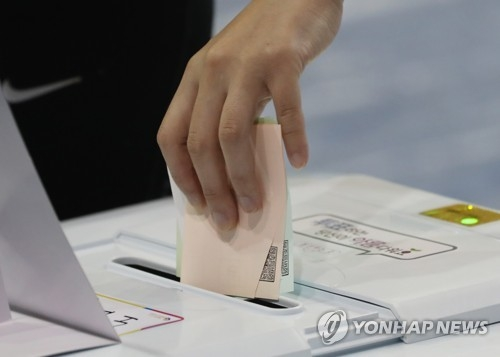 This photo taken on June 13, 2018, shows a voter putting his or her ballots into a voting box for the local elections. (Yonhap)