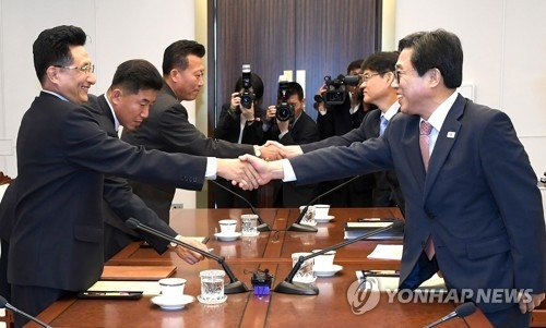 In this photo provided by the sports ministry, representatives from South Korea (R) and North Korea shake hands before the start of their sports talks at the Peace House, located on the southern part of the truce village in Panmunjom, on June 18, 2018. (Yonhap)