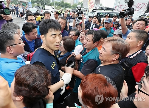 Merchants and enforcement officers clash over the latter's attempt to carry out a forced order to relocate shops to a new building in front of the Noryangjin Fisheries Wholesale Market in Seoul on July 12, 2018. (Yonhap)