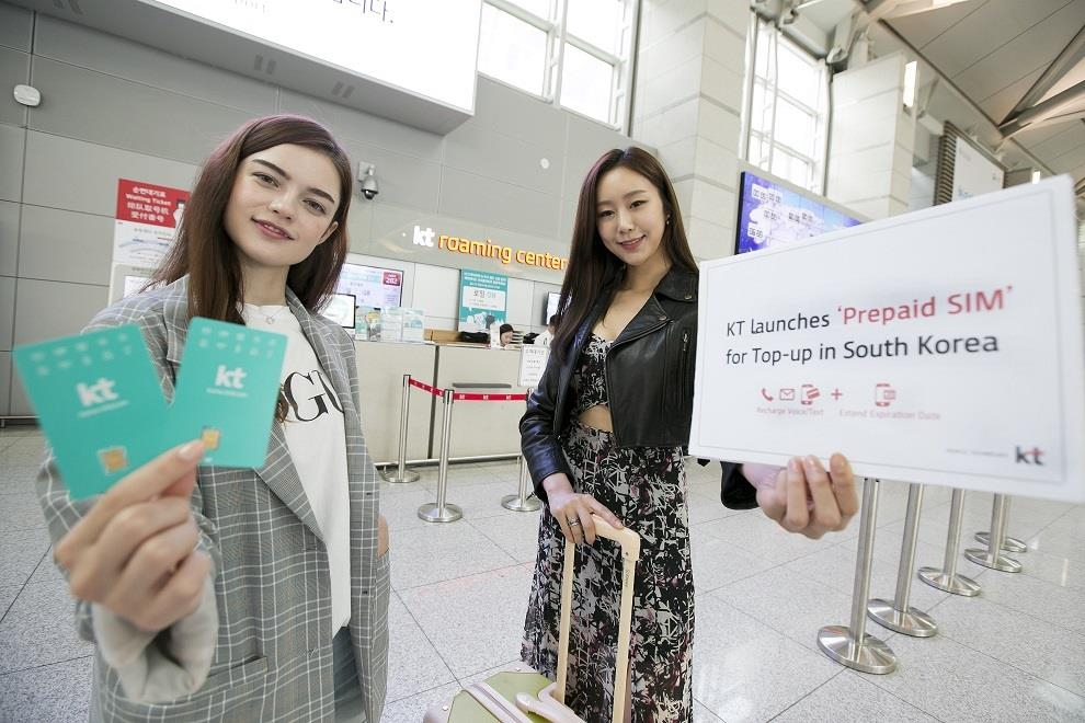 Models pose with KT Corp.'s top-up SIM card in this photo provided by the company on Oct. 12, 2018. (Yonhap)