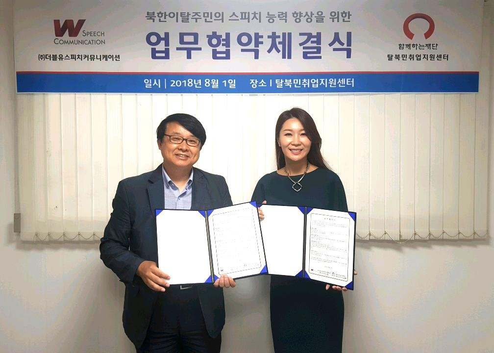 This photo provided by W Speech Communication shows its head, Woo Ji-eun (R), and Choi Kyung-il, head of the North Korean Refugee Employment Support Center posing together after signing a deal to cooperate in supporting North Korean defectors on language training. (Yonhap)