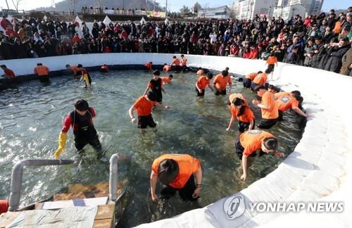 Tourists trying to catch trout with bare hands (Yonhap)