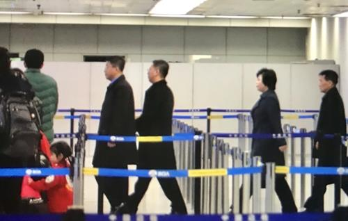 North Korean officials walk to board a plane bound for Hanoi at the Beijing international airport on Feb. 20, 2019. (Yonhap)