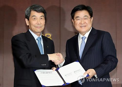KDB chairman Lee Dong-gull (L) shakes hands with Hyundai Heavy Industries vice chairman Kwon Oh-gap after signing a deal on Daewoo Shipbuilding & Marine Engineering Co. at KDB's headquarters in Seoul, on March 8, 2019. (Yonhap)
