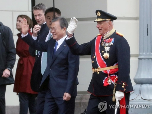South Korean President Moon Jae-in (L) and King Harald V of Norway wave during an official welcoming ceremony at the royal palace in Oslo on June 12, 2019.