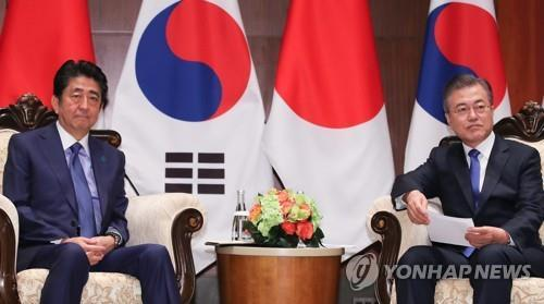 South Korean President Moon Jae-in sits down with Japanese Prime Minister Shinzo Abe in this undated file photo. (Yonhap)