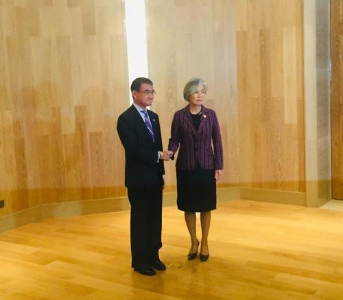 Foreign Minister Kang Kyung-wha shakes hands with her Japanese counterpart, Taro Kono, before their talks in Beijing on Aug. 21, 2019. (Pool photo) (Yonhap)