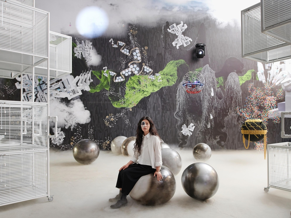 "This image of artists Yang Hae-gue against the backdrop of her exhibition ""When The Year 2000 Comes"" at Kukje Gallery is provided by the gallery. (PHOTO NOT FOR SALE) (Yonhap)"
