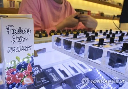 A clerk at an e-cigarette store in Seoul introduces products. On Oct. 23, 2019, Health Minister Park Neung-hoo strongly advised people not to use liquid-type e-cigarettes, citing health risks. (Yonhap)