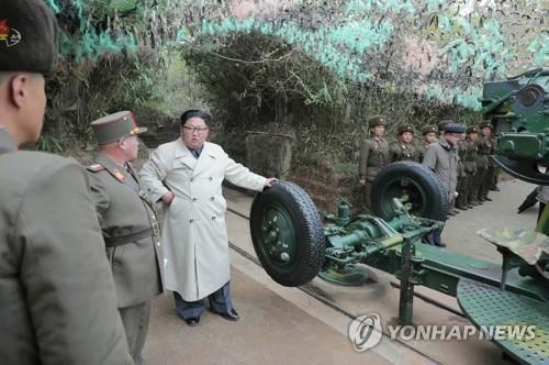 Putting his hand on military equipment believed to be a coastal gun, North Korean leader Kim Jong-un (3rd from L) talks with soldiers during a visit to a defense detachment on Changrin Islet near the western sea border with South Korea, in this photo provided by the Korean Central News Agency on Nov. 25, 2019. The agency stopped short of reporting when he made the visit. (For Use Only in the Republic of Korea. No Redistribution) (Yonhap)
