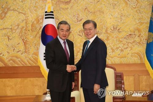South Korean President Moon Jae-in (R) shakes hands with visiting Chinese Foreign Minister Wang Yi during the latter's courtesy call at the presidential office in Seoul on Dec. 5, 2019. During the talks, Moon expressed gratitude for the Chinese government's contribution to peace on the Korean Peninsula. (Yonhap)