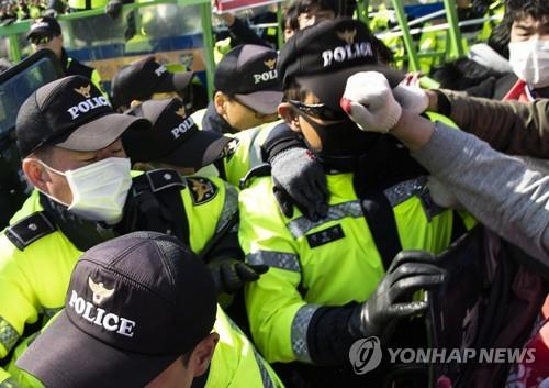 This file photo, dated April 3, 2019, shows a police officer being struck in the face by Korean Confederation of Trade Unions members during their protest against a labor law revision in front of the National Assembly in Seoul. (Yonhap)